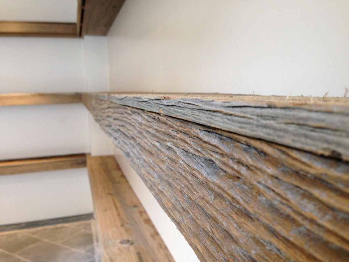 Mise en place de vieux bois de planche canadienne de sapin pour réaliser des étagères chez un fleuriste.